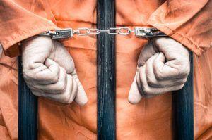 handcuffed prisoner behind bars   Child Sex Assault in Boulder