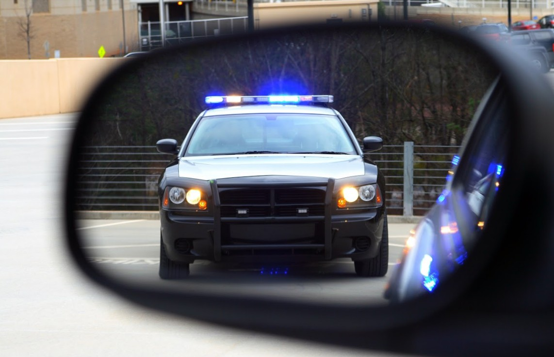 a close up photo of a police car as viewed from a car's side mirror | probable cause and reasonable suspicion