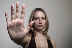 blonde woman holding hand out to say stop | Differences Between Sexual Harassment and Sexual Assault