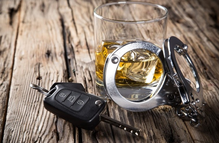close up photo of handcuffs, glass of alcohol and car keys | types of alcohol tests