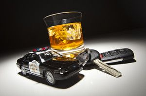 Highway Patrol Police Car Next to Alcoholic Drink and Keys Under Spot Light | Colorado Criminal Penalties for DUI Offenses