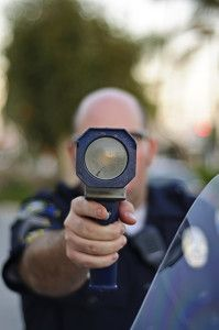 cop pointing radar gun - Are Fees From Minor Violations Bleeding Lower Income Citizens Dry?