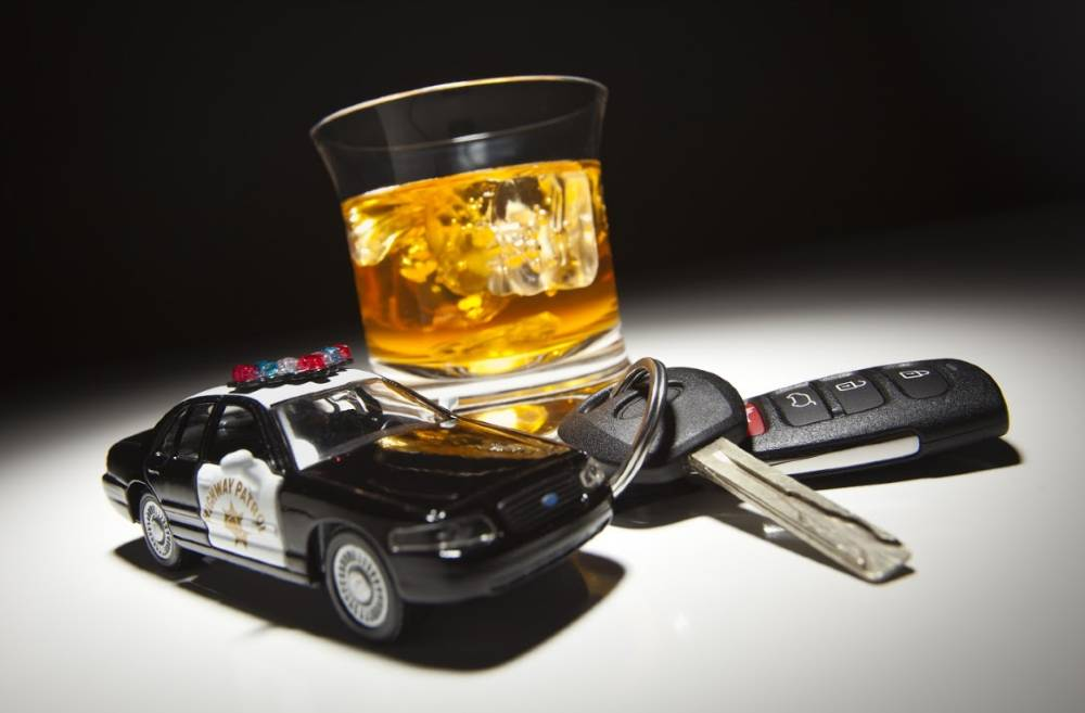 glass of alcohol beside car keys and a toy police car | the heat is on dui enforcement campaign