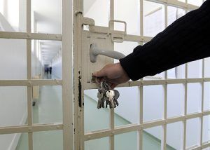 guard with keys opening Prison cell | Injustice in the Justice System