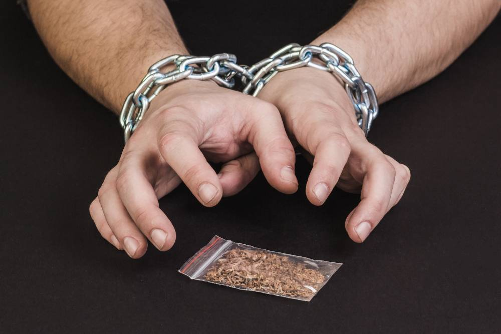 hands of a man in chains trying to reach for a sachet of drugs | drug-related crimes in boulder