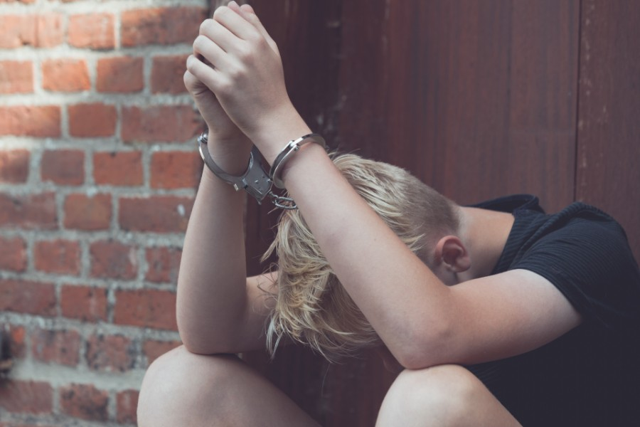 young teen on handcuffs while looking down | Juvenile Justice System in Boulder
