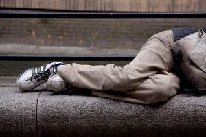 the legs of a homeless person asleep on a bench | Do Homeless Laws Criminalize Poverty