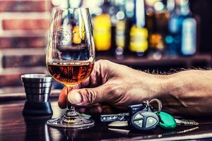 man holding glass of liquor on bar next to dram and keys | Colorado is the 21st Worst State for DUI