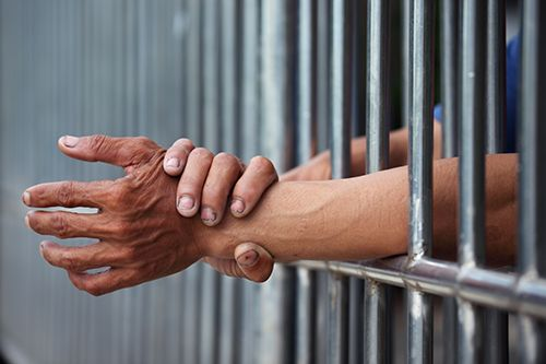 man rubbing his wrist arms between jail cell bars | Long-Term Consequences of a Criminal Conviction