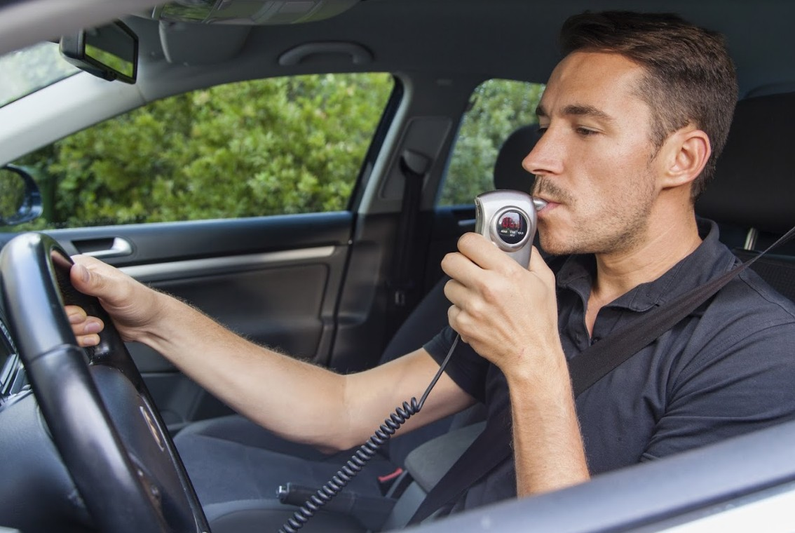man using a breathalyzer inside his car | consequences of a dui in colorado