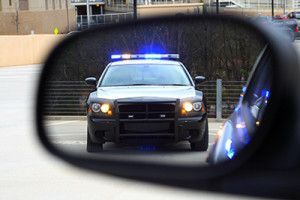 Traffic stop with police car in driver side rear view mirror | Traffic Stop Tips That Will Help You Protect Your Rights