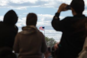 Silhouettes of travelers looking at the flag of the United States of America | How Dangerous are Immigrants